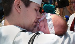 800px-US_Navy_040723-N-9288T-309_A_father_holds_his_newborn_child_upon_his_arrival_to_San_Diego_aboard_USS_Ronald_Reagan_(CVN_76)